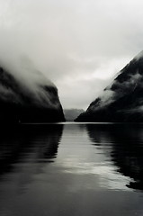Doubtful Sound (AndrewNZ) Tags: newzealand cloud reflection 2004 nature topf25 topv111 topv2222 wow topf50 topv555 topv333 topf75 topv1111 interestingness1 january peaceful calm sound fjord topv777 brooding wilderness topv3333 topf100 aotearoa doubtful fiord looksblackandwhitebutwasshotoncolourfilm doubtfulsound topv888 fiordland interestingness2 i500 explore3aug04 worldheritagearea