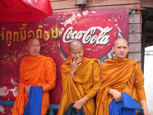 Monks in front of Coke sign