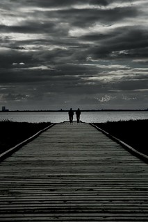 Silhouette Of Couple Walking To The Water