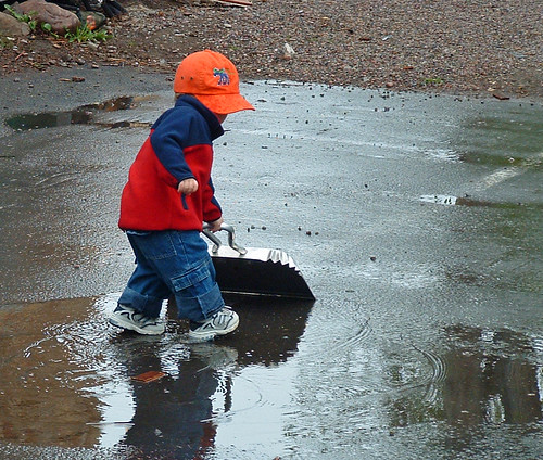 child sweeping rain