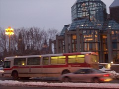A MCI Classic TC40102 bus in front of the National Gallery of Canada. (Steve Brandon) Tags: road street city windows ontario canada trafficlights building bus art cars glass museum architecture painting spectacular geotagged photography photo twilight downtown gallery glow publictransit publictransportation traffic artgallery dusk steel ottawa arts skylight scenic parliament structure granite autos publictransport circulation atrium autobus parliamenthill gmc automobiles ville centreville taillights modernist colonnade voitures peacetower brakelights tomgreen moshesafdie nationalgalleryofcanada canadianparliament sussexdrive sussexdr octranspo majorshillpark parliamentarylibrary   musedesbeauxartsducanada novabus mciclassic  feuxdecirculation tc40102a tc40102n promenadesussex moishesafdie parkinsafdiearchitectsplanners tigerzebra tc40102