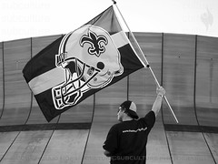 The Saints Come Marching Home (Culture:Subculture) Tags: blackandwhite usa photography la football education flag neworleans fineart helmet documentary hurricanekatrina fleurdelis forsaken falcons superdome subculture craigmorse cu