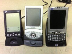Three PDAs in cradles