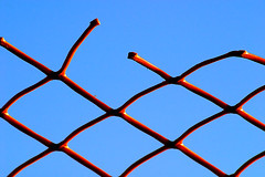 containment breach (♫ marc_l'esperance) Tags: blue sky orange abstract color colour geometric broken colors vancouver contrast fence saturated pattern break colours geometry 2006 plastic repetition link barrier fencing abstraction nocrop asymmetry uncropped linked cml contrasting aplusphoto abigfave canonef100300mmf56 canon eos 10d minimalism minimalist abstractart © allrightsreserved luxmaticcom