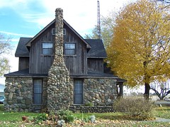 Country house (Valerie Everett) Tags: wood old flowers blue trees sky orange brown house stone clouds yard trunk twostory antenna
