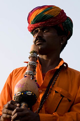 Kalbelia Dance Troupe Leader, Rajasthan, India (Captain Suresh Sharma) Tags: life wood old travel red portrait people music india man art heritage history tourism festival shirt rural pose fun person design wooden costume ancient community asia artist dress action folk vibrant character indian traditional religion group decoration performance culture belief gear folklore dancer grace east clothes event entertainment gourd instrument leader nomad local turban tradition musicalinstrument tribe custom ethnic eastern folkdance jaipur streetshow cultural rajasthan indigenous multicolour lively entertain treet troupe attire spirited kalbelia snakecummunity