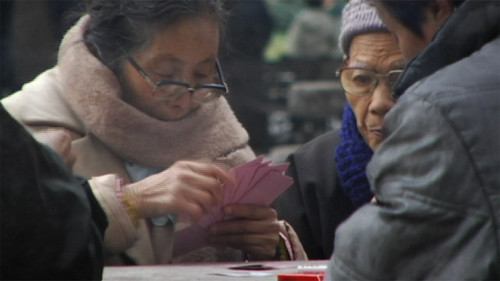 Lady playing cards in Shanghai, bundled up.