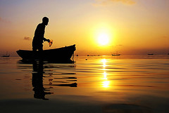 fisherman (muha...) Tags: ocean sunset reflection water work island fisherman bravo smoking maldives sihouette islandlife abigfave