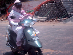 woman wearing hijab riding a scooter