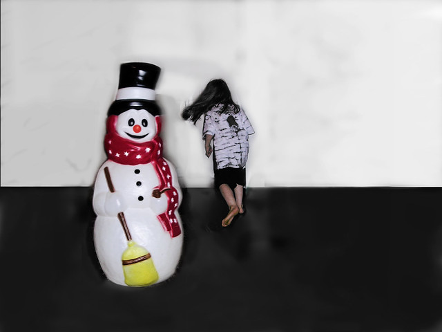 The child plays at making friends with a snowman