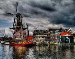Haarlem Scenery (Howland Studio) Tags: holland haarlem topf25 windmill beautiful dutch clouds wow river boats fantastic scenery 500v20f scenic thenetherlands dramatic surreal stormy dreamy riverfront hdr stormysky molen cloudysky dutchwindmill stormyskies cotcmostfavorited tonemapping deadriaan hdrsingleraw abigfave hdrextremes p1f1 haarlemholland dutchboats saarneriver saarne molendeadriaan excellentphotographerawards