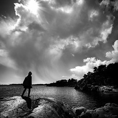 Salvation at Journey's End (Kurt Evensen) Tags: awe grand mighty water clouds norway sun light jump silhouette monochrome devinity bw nature rocks beam sunbeam ocean blackandwhite sea shore austagder no