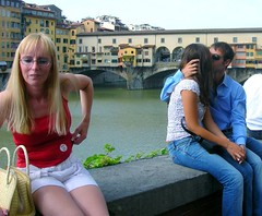 a blonde girl, a sweet kiss and ponte vecchio (loungerie) Tags: bridge red people girl glasses florence kiss couple sitting ponte sit romantic firenze seated bacio intimacy pontevecchio ragazza streetshot kisser bionda