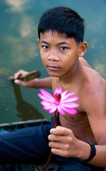 Water Lily Boy (jerikojosh) Tags: boy flower water digital canon boats cambodia cambodian village child waterlily bokeh working young angkorwat zen 5d charming survival villager villagelife 70200mmf28l inquisative abigfave impressedbeauty childrenofangkorwat earthasia