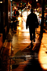 rainy night ( marc_l'esperance) Tags: street light shadow orange woman color colour texture wet colors rain silhouette yellow night vancouver canon reflections dark walking concrete eos gold lights golden glow colours shadows dof traffic bokeh  2006 surface sidewalk rainy 10d reflective boke commercialdrive towards allrightsreserved approaching eastvancouver cml gvrd thegallery canonef70200mmf28lusm ef70200mmf28l canon70200f28l