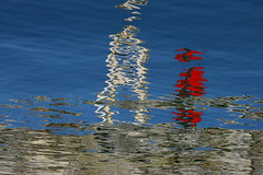 Man in Red Walking Past Lighthouse Beacon (rldock) Tags: abstract reflection water vancouver