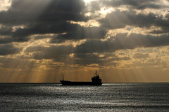 Ship in Sunbeams (Geoff Penn) Tags: sea cloud sun sunlight silhouette clouds sussex boat flickrbadge brighton ship spotlight seashore shining glint shoreham crepuscularray shorehamharbour godsrays supermasterpiece
