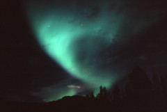 Aurora Borealis: Funnel (storm light) Tags: red sky canada green stars glow bc oxygen fluorescent midnight planet curtains rays nitrogen luminous arcs atmospheric funnel constellation atoms northernlights auroraborealis molecules phenomenon electrons magneticfield toadriver solarelectrons magneticpoles auroraloval ionospere