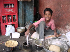 Almost lunch time (Eileen Delhi) Tags: boy urban india cooking smile face kids work dough delhi altruism redandblue 600views roti indianportrait cotcmostinteresting inhonorof interestingness94 realindia i500 utatafeature
