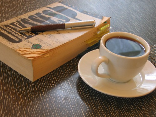 Ulysses by James Joyce book pen on it and cup of tea.