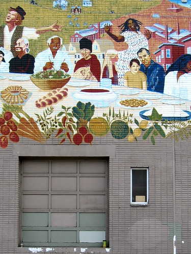 graffiti on brick -- group of people, joyous, sitting at a table set with bread and vegetables