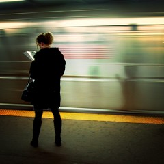 On the platform, reading (moriza) Tags: city nyc newyorkcity woman newyork yellow wow underground subway reading alone metro stripes 100v10f mo motionblur solitary bigapple mohammad moriza riza subterranian mamat lonefigure 14thstreetstation interestingness7feb2006 abigfave modomatic