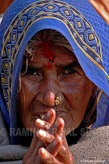A Sadhvi or The Holy Woman (Raminder Pal Singh) Tags: street old travel blue portrait people woman india color heritage face saint female hair asian outside person grey see design eyes hands asia pattern dress emotion display outdoor expression robe indian traditional faith prayer religion pray poor culture belief east holy health shade wise devotion sacred yogi ritual express aged fold feeling thin punjab custom devotee ethnic hindu hinduism eastern wrinkles sari pilgrimage amritsar priestess humble pilgrim ascetic bindi austere pious godly attire caste saintly spiritualism thepca tilak sadhvi holy woman nosepin senior citizen