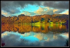 Autumn on Grasmere (adrians_art) Tags: blue autumn trees light red england sky green water tag3 clouds reflections dark geotagged landscapes bravo tag2 tag1 seasons grasmere lakes cumbria naturesfinest geotags magicdonkey instantfave outstandingshots specland abigfave flickrdiamond bratanesque