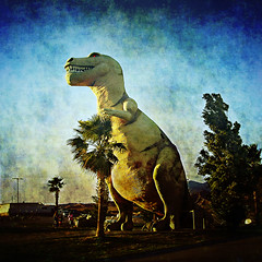 dinosaur. cabazon, ca. 2005. (eyetwist) Tags: 2005 road usa america photoshop square concrete desert dino dinosaur roadtrip reststop palmtree americana roadside i10 processed vignette trex tyrannosaurus cabazon tyrannosaur supersaturated postprocessing lensblur secretrecipe eyetwist prcssd contactforstockusage thisimagemaybeavailableforlicensecontactformoreinfo
