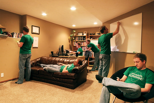 Young man in green Illinoise t-shirt in his room office with the multiplicity effect