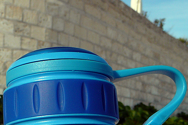 A close-up of of the blue lid of a water bottle sitting on the beach.  Mostly me testing out the macro feature on my new camera.