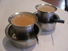 Masala tea in a metal cup inside a metal bowl