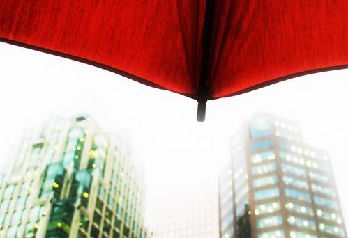Fotografía tomada desde un paraguas rojo, tras él dos edificios entre la luz