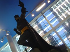 batman jumping against a background of a shiny skyscraper in daytime