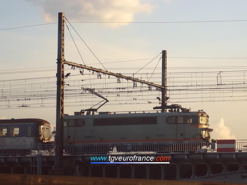 Coucher de soleil sur une locomotive électrique BB 9600 SNCF franchissant le Rhône en pousse d'une rame RIO assurant une liaison TER Mâcon - Lyon