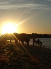Folks Walking Along Cowes Beach At Sunset