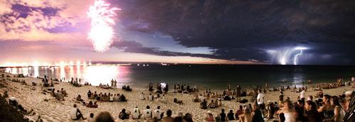 Playa australiana con fuegos artificiales, tormenta y un cometa en medio