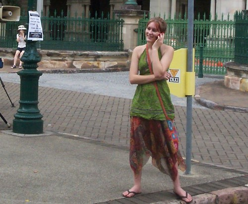 On the phone - attendee at Invasion Day Rally and March, Parliament House, George St, Brisbane, Queensland, Australia 070126