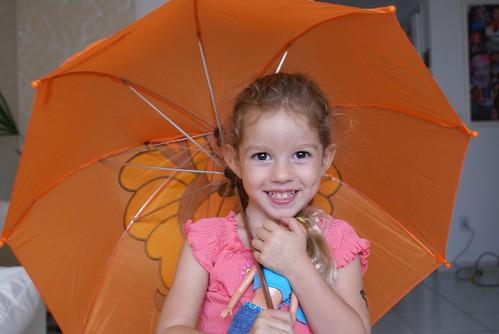 Yohanah com um sorriso muito bonito e sombrinha laranja, numa foto tirada pelo vovô Nelson