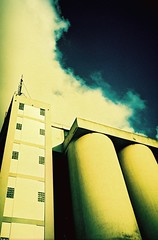 Who's the operator (bricolage.108) Tags: cloud building industry xpro crossprocess xa2 silos olympusxa expiredfilm