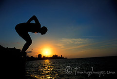 A diver leaps into the sea from the Malecon at sunset (tommyimages_com) Tags: ocean sunset sea male latinamerica horizontal fly jump risk havana cuba flight dive free seawall waters caribbean diver blueskies cuban habana leap soar lahabana elmalecn elmalecon ciudaddelahabana takeachance