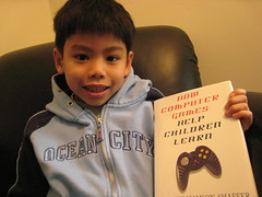 smiling kid holding video game learning book