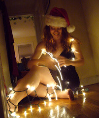 Merry Christmas 3 (QXZ) Tags: christmas light party portrait woman holiday cute girl beautiful beauty brooklyn pose glamour pretty december tara feminine seasonal posed 2006 hallway christmaslights sparkle actress santahat tangle blackdress woodflooring extrovert