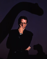 Michael Crichton with a dinosaur in the background