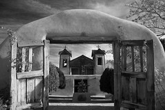 Sanctuario de Chimayo (Tom Haymes) Tags: trees blackandwhite bw cloud newmexico building church architecture clouds rural gate cross decay country rustic symmetry historic belltower steeple adobe pilgrimage anseladams chimayo countrychurch thegalleryoffinephotography