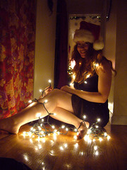Merry Christmas (QXZ) Tags: christmas light party portrait woman holiday cute girl beautiful beauty brooklyn pose glamour pretty december tara feminine seasonal posed 2006 hallway christmaslights sparkle actress santahat tangle blackdress woodflooring extrovert
