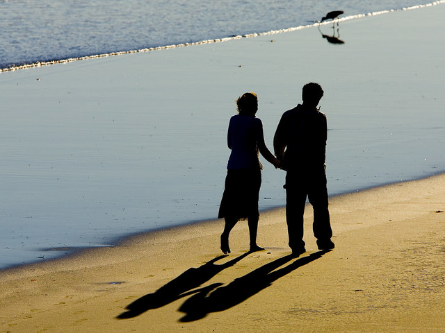 19, 2006 Two people walk holding hands on the beach at low tide south of