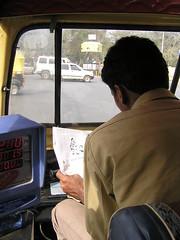 Conductor de rickshaw leyendo el periódico