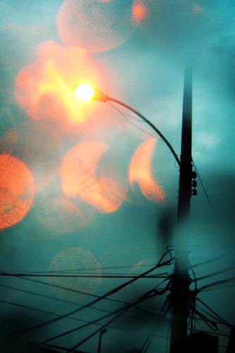 Fotografía de una farola en un día de lluvia, las gotas sobre el objetivo generan glares anaranjados