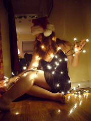 Merry Christmas 5 (QXZ) Tags: christmas light party portrait woman holiday cute girl beautiful beauty brooklyn pose glamour pretty december tara feminine seasonal posed 2006 hallway christmaslights sparkle actress santahat tangle blackdress woodflooring extrovert